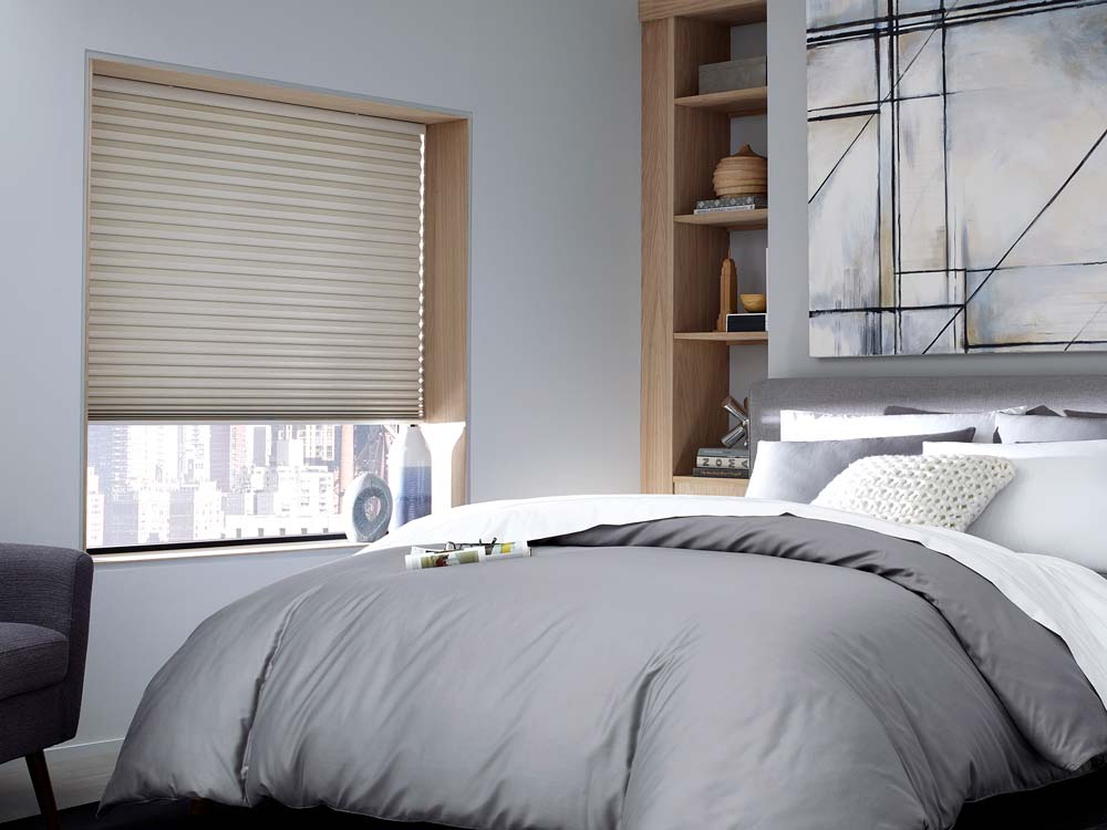 Soothing bedroom decor featuring grey tones and cellular shades